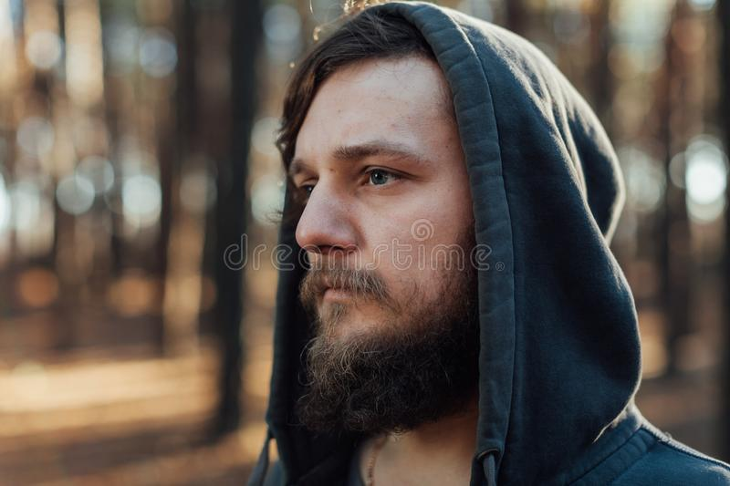 A young man with a beard walks in a pine forest. Portrait of a brutal bearded man in a hood stock photos