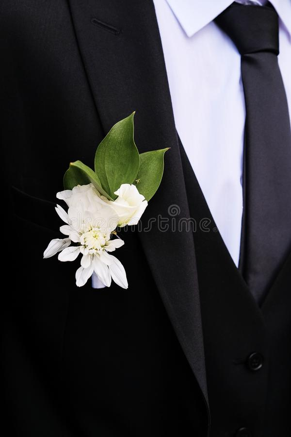 Young man with a beautiful boutonniere of white roses or chrysanthemums and green leaves, on the lapel of his jacket. The groom in stock images