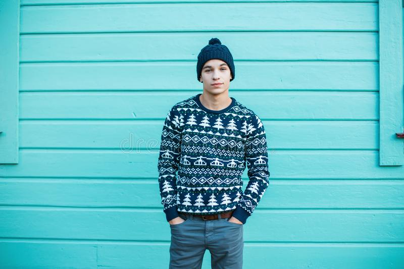 Young man with a beautiful smile in a knitted hat with blue eyes in a blue Christmas vintage sweater in jeans stands in the city. Near a bright blue wooden royalty free stock image