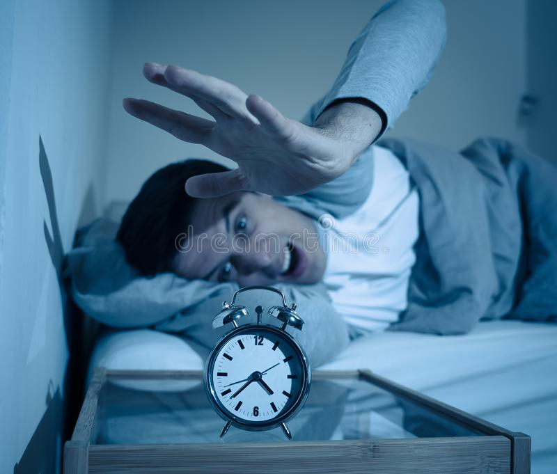 Young man in bed with alarm clock feeling desperate and distress not able to sleep with insomnia royalty free stock images