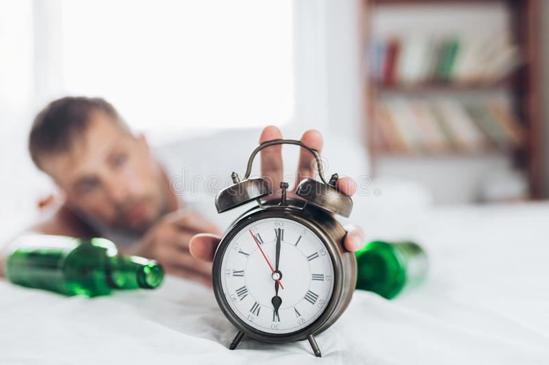 Young man in bed the morning after night out drinking royalty free stock photos
