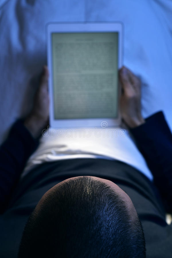 Young man in bed reading an e-book in his tablet stock photos