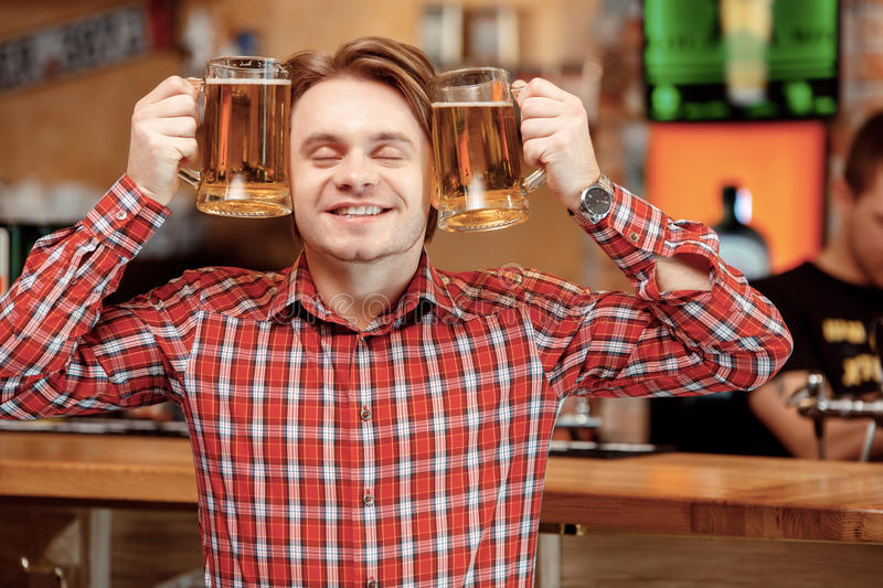 Young man with beer mugs. Happy together with friends. Young cheerful man holding two mugs with beer by his face and smiling with closed eyes royalty free stock photos