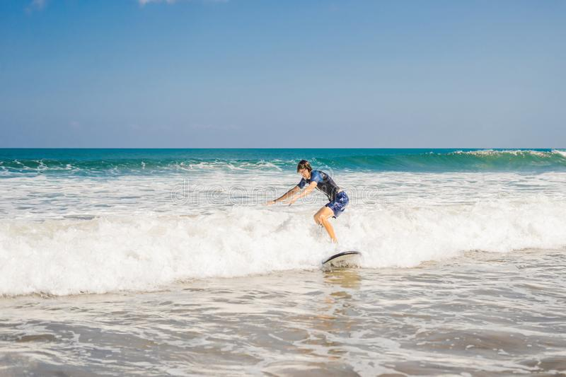 Young man, beginner Surfer learns to surf on a sea foam on the B royalty free stock photography
