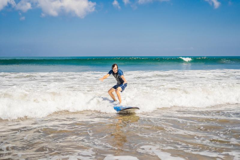 Young man, beginner Surfer learns to surf on a sea foam on the B stock photo