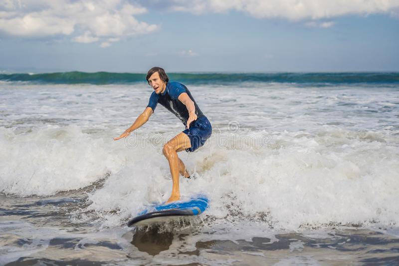 Young man, beginner Surfer learns to surf on a sea foam on the B stock image