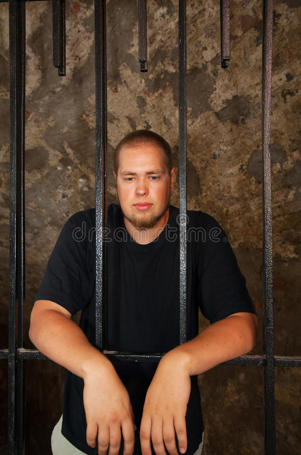 Young man behind the bars. Young man looking from behind the bars stock images