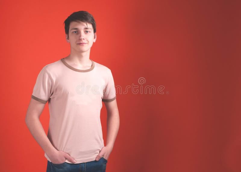 Young man in beige t shirt standing with hands in pockets and looking at camera on coral color background stock image