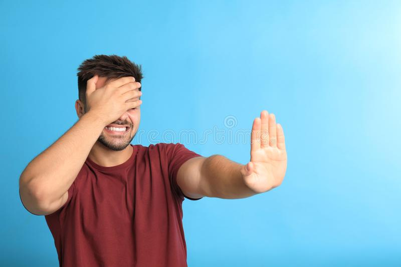 Man being blinded on blue background. Young man being blinded on blue background stock photo