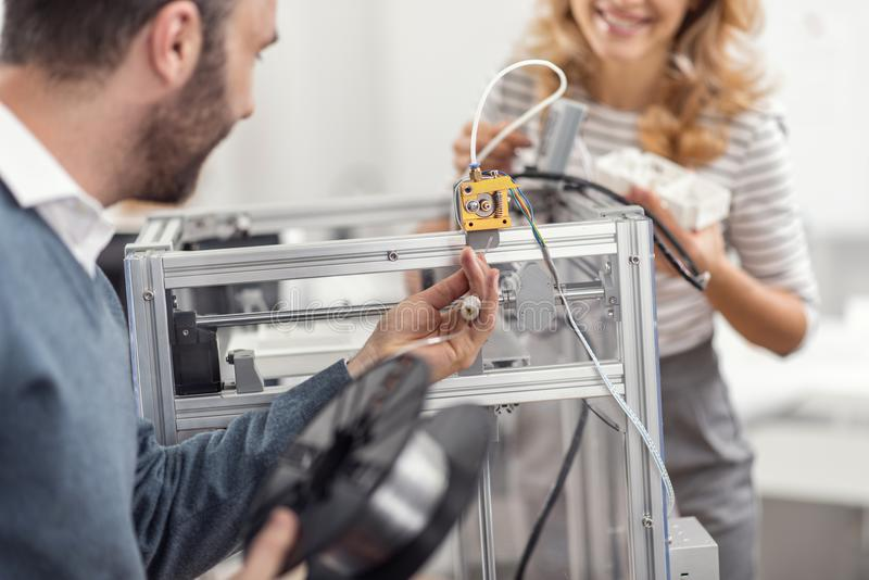 Young man being about to insert filament into extruder. Mastered skills. Pleasant young men being about to insert the filament into the extruder of a 3D printer royalty free stock photos