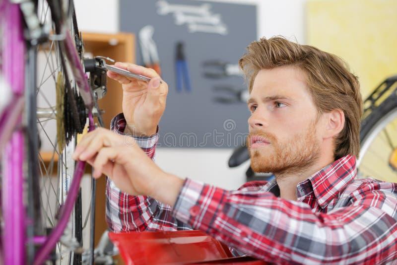 Young man bicycle mechanic repairing bicycles stock photo