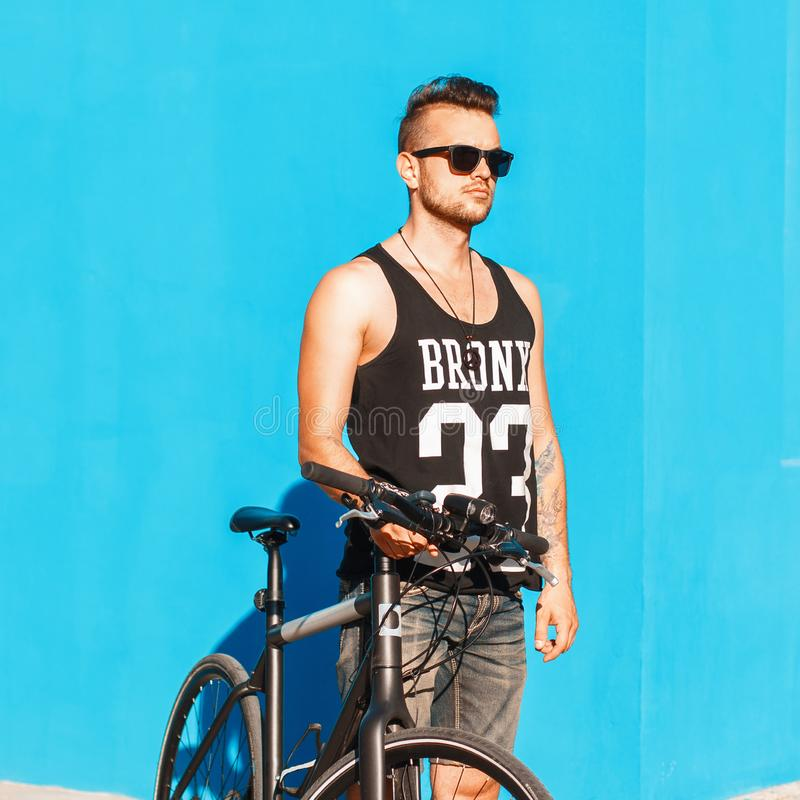 Young man with a bicycle near a bright blue wall. T-shirt with t stock photo