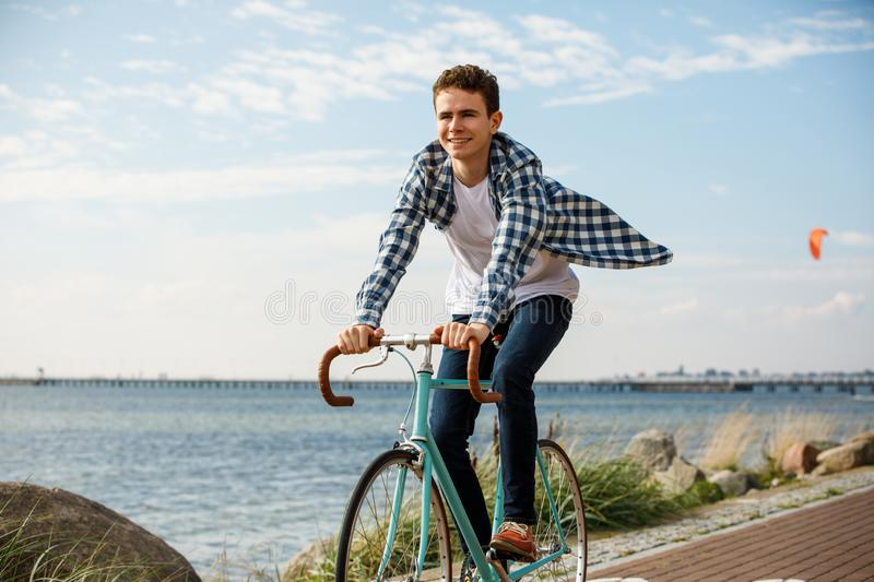 Young man biking at seaside. Healthy lifestyle - happy man riding bicycle stock photography
