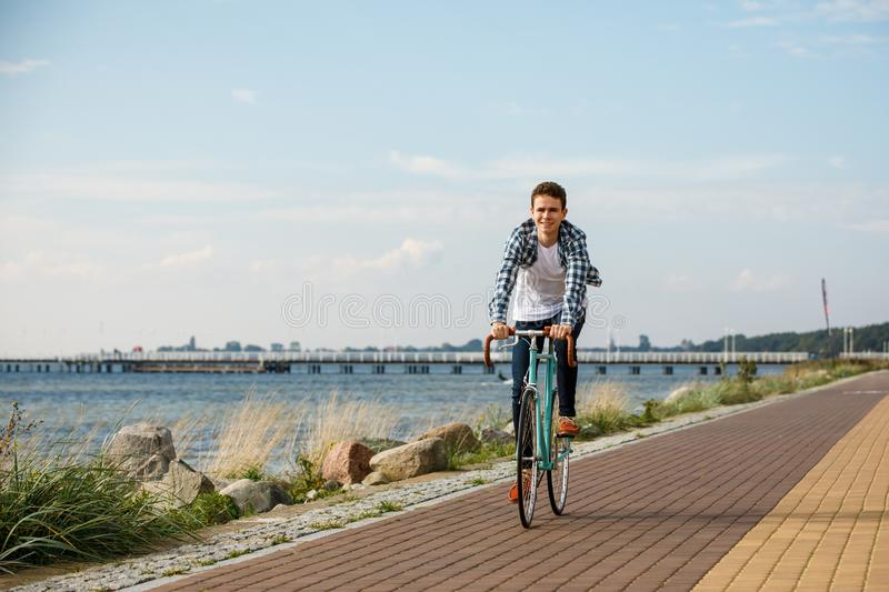 Young man biking at seaside. Healthy lifestyle - happy man riding bicycle stock photos