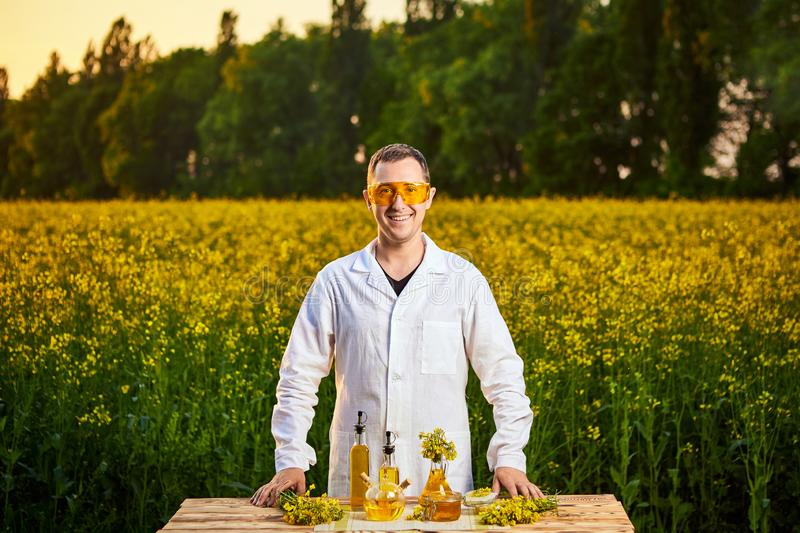 A young man biologist or agronomist examines the quality of rapeseed oil on a rape field. Agribusiness concept stock image