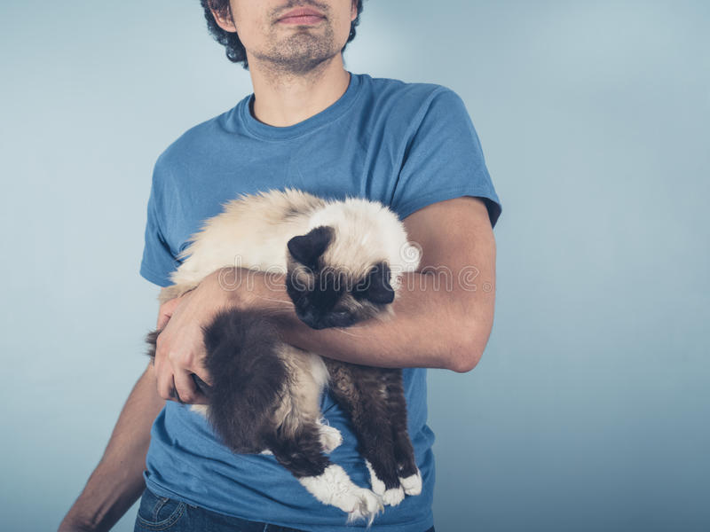 Young man with Birman cat stock photo