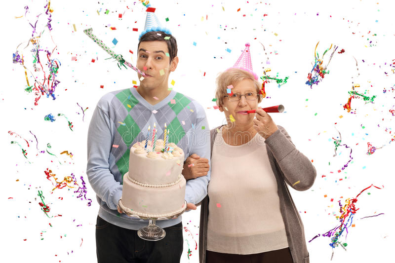 Young man with birthday cake and mature woman blowing party horn. Young men with a birthday cake and a mature women blowing party horns isolated on white stock photo