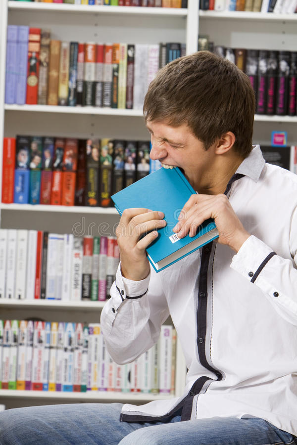 Young man bite a book royalty free stock photo