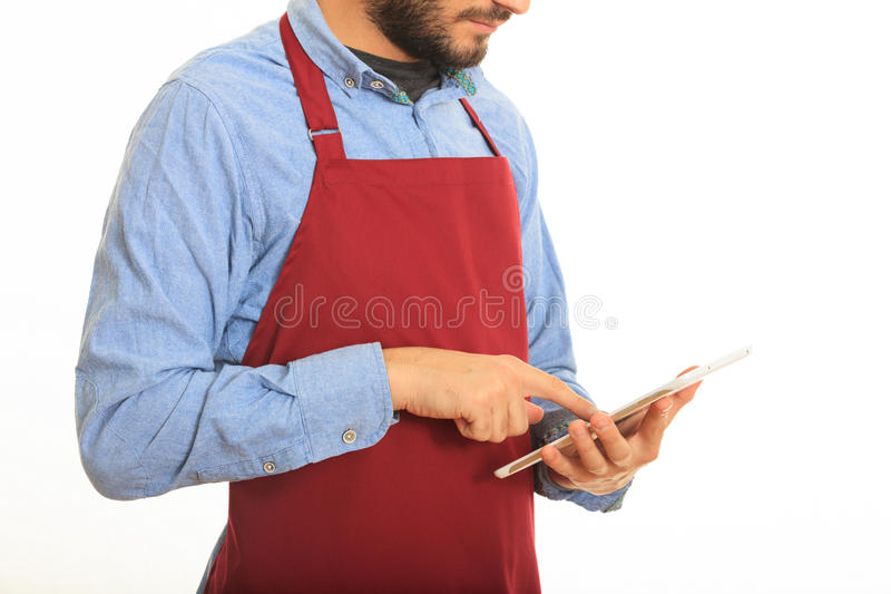 Young man with black apron taking an order. On white background royalty free stock photography