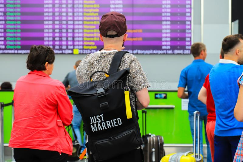 A young man with a black bag with the inscription - just married is standing near a information board about arrival and departure stock image