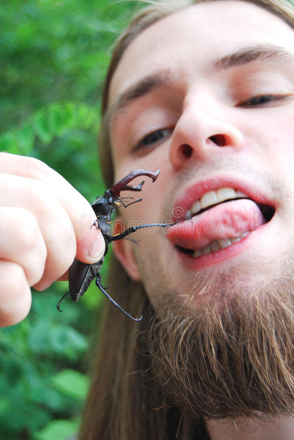 Young man with a black beetle. Portrait of young man with a black beetle outdoors stock image