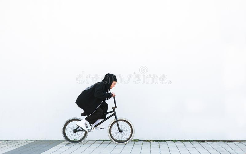 Young man in a black casual clothing rides a bmx bike on the background of a white wall stock photography