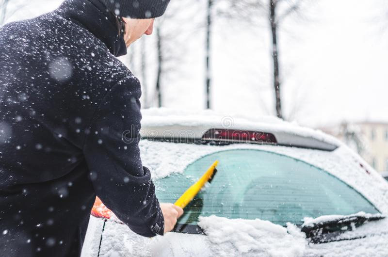Man cleans his car from the snow. Young man in black coat cleans his car with yellow brush during snowfall. Winter inclement weather royalty free stock photos