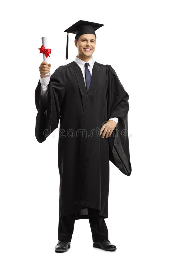 Young man in a black graduation gown and cap holding a diploma. Full length portrait of a young man in a black graduation gown and cap holding a diploma isolated royalty free stock photos