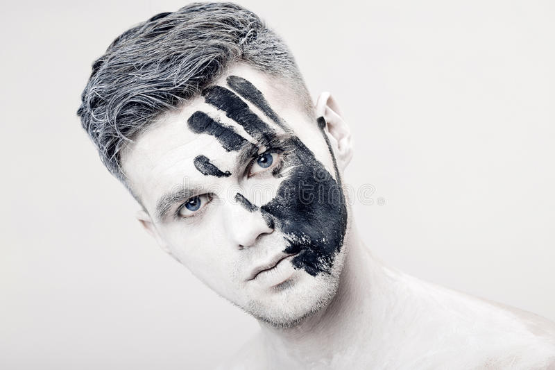Young man with black hand print on white face. Closeup Portrait. Professional Fashion Makeup. fantasy art makeup royalty free stock images