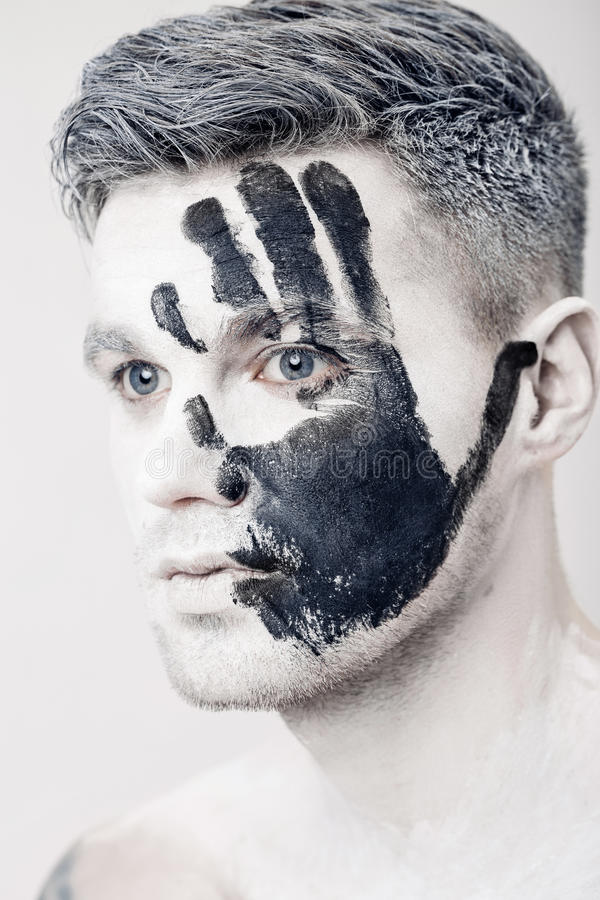 Young man with black hand print on white face. Closeup Portrait. Professional Fashion Makeup. fantasy art makeup. Young man with black hand print on his white royalty free stock image