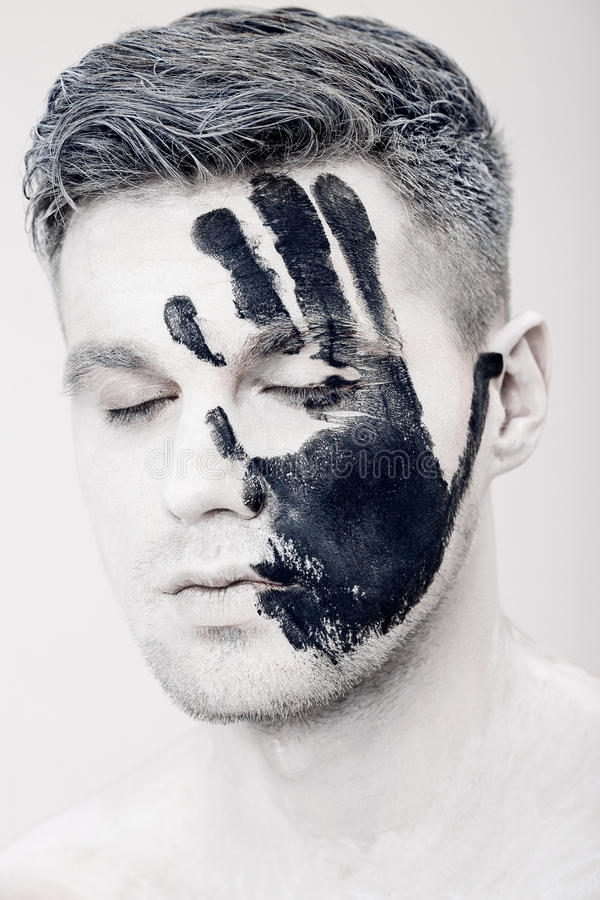 Young man with black hand print on white face. Closeup Portrait. Professional Fashion Makeup. fantasy art makeup royalty free stock photo