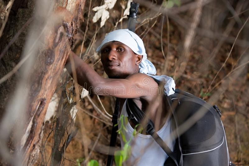 Close up of young man in the countryside. Young man in black jeans backpack with head tied up standing in bush looking at the camera stock photo