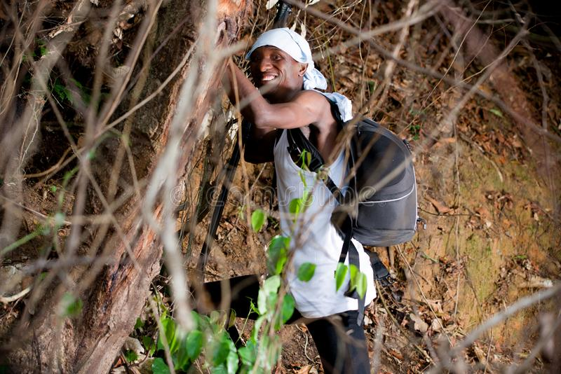 Portrait of young man in the countryside, happy. Young man in black jeans backpack with his head tied up standing in bush looking at camera smiling royalty free stock image
