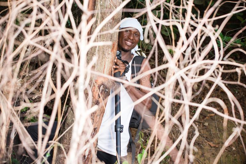 Portrait of young man in the countryside, happy. Young man in black jeans backpack with his head tied up standing in bush looking at camera smiling stock image