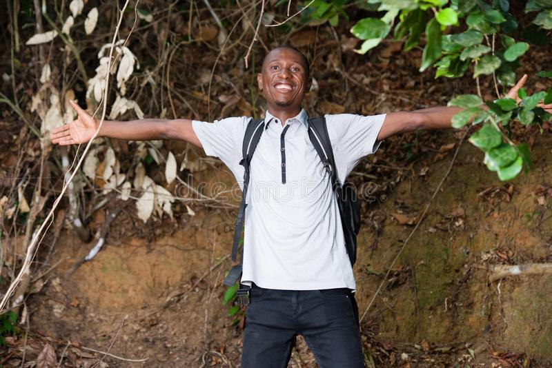 Portrait of young man in the countryside, happy. Young man in black jeans standing with backpack laughing while looking at the camera royalty free stock photo