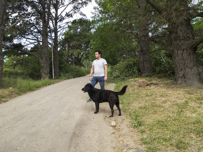 Young man with a black labrador dog, both looking to the side. Tandil, Buenos Aires, Argentina royalty free stock images