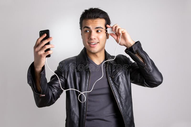 Man charges the phone from the head. A young man in a black leather jacket charges your cell phone from the head. the concept of the new technology royalty free stock photo