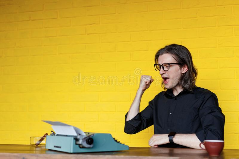 Portrait of a man in black shirt glass, showing successful, seated at a table near typewriter over yellow background. royalty free stock photos