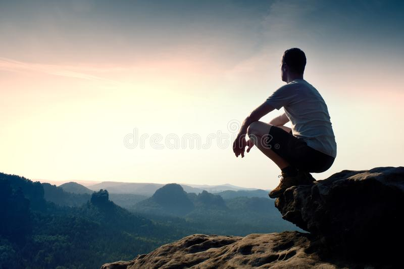 Young man in black sports pants and grey shirt is sitting on cliff's edge and looking to misty valley bellow. Young hiker in black pants and shirt is sitting on royalty free stock images