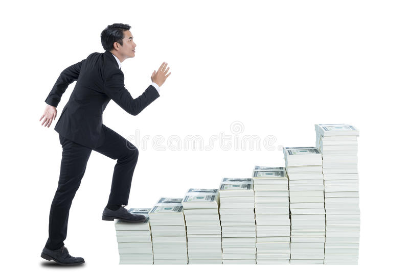 The young man in black suite is walking on stack of banknote like up stair stock image