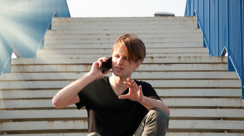 Young man explaining something complicated, while talking through the phone, sitting on the stairs with blue fence royalty free stock photo