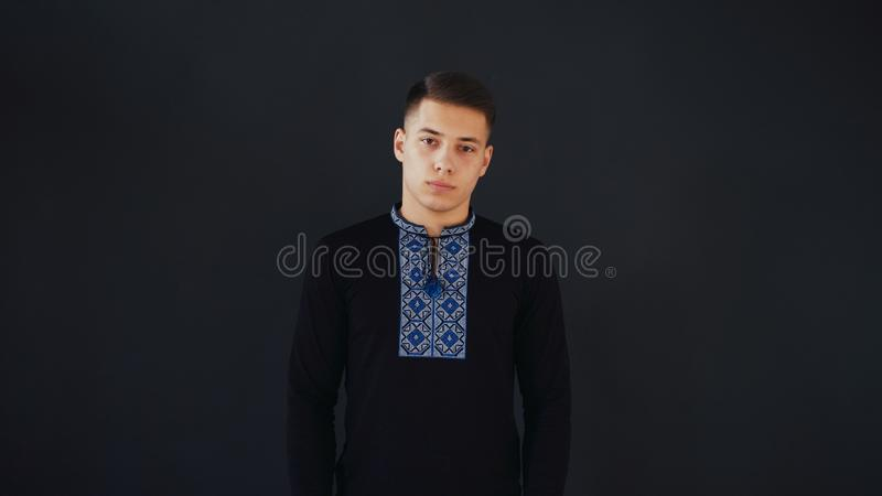Young man in black vyshyvanka stands and looks on camera. Young man is calm and peaceful royalty free stock photo
