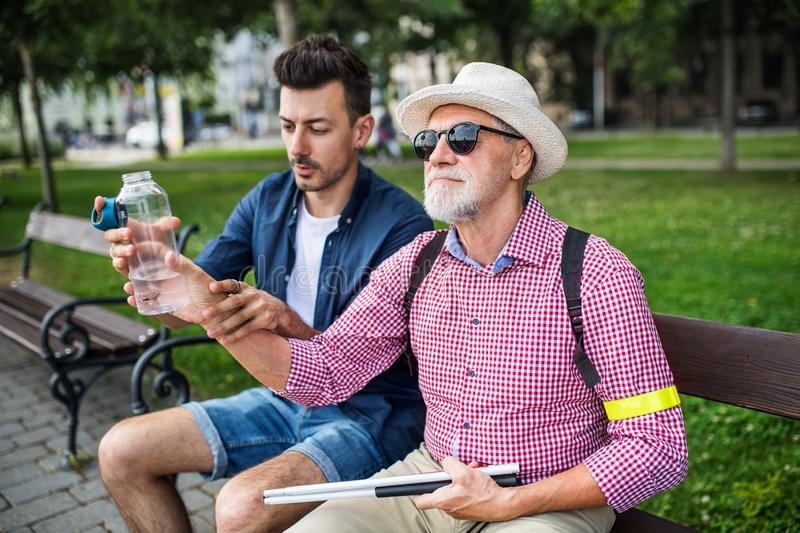 Young man and blind senior with white cane sitting on bench in park in city. royalty free stock photography