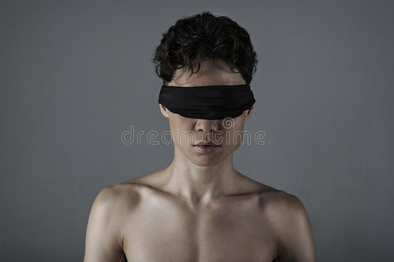 Young man with a blindfold. Young man of Asian appearance with a blindfold royalty free stock photography