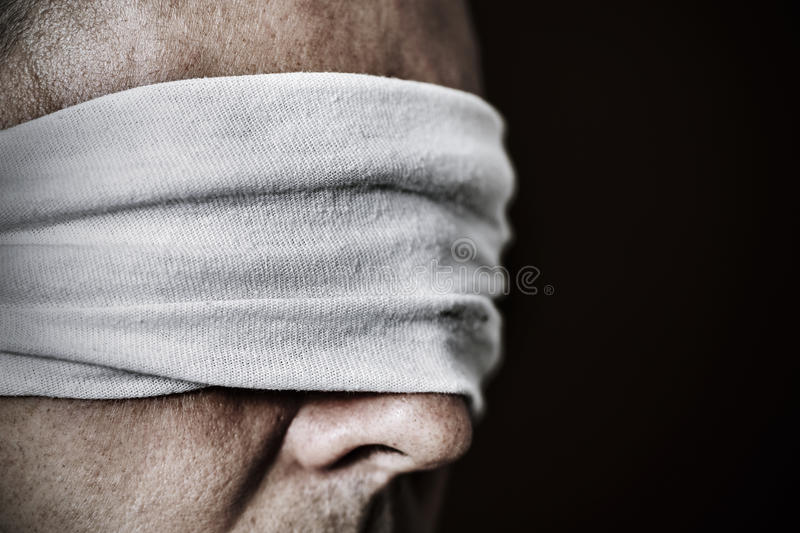 Young man with a blindfold in his eyes. Closeup of a young man with a blindfold in his eyes, as a symbol of oppression or repression, with a dramatic effect stock photography