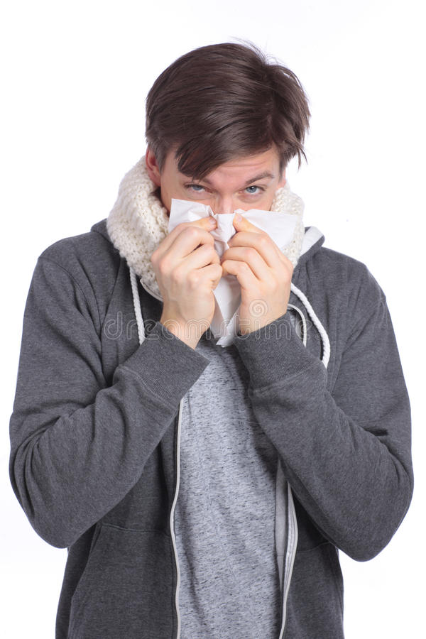 Young man blowing his nose royalty free stock image