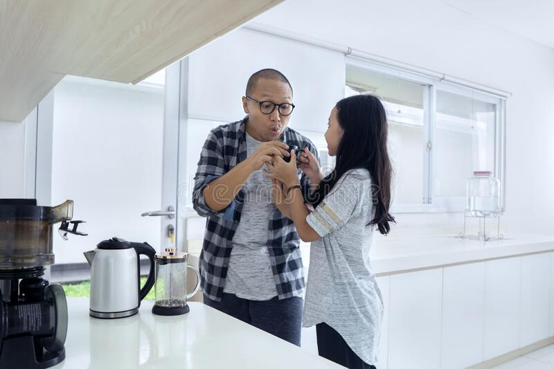 Young man blowing a hot coffee from his daughter stock photo