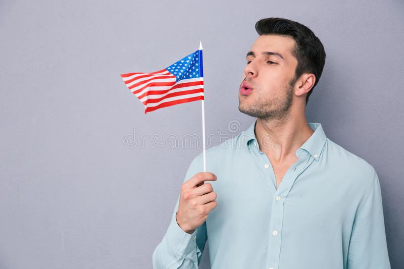 Young man blowing on US flag. Over gray background royalty free stock image