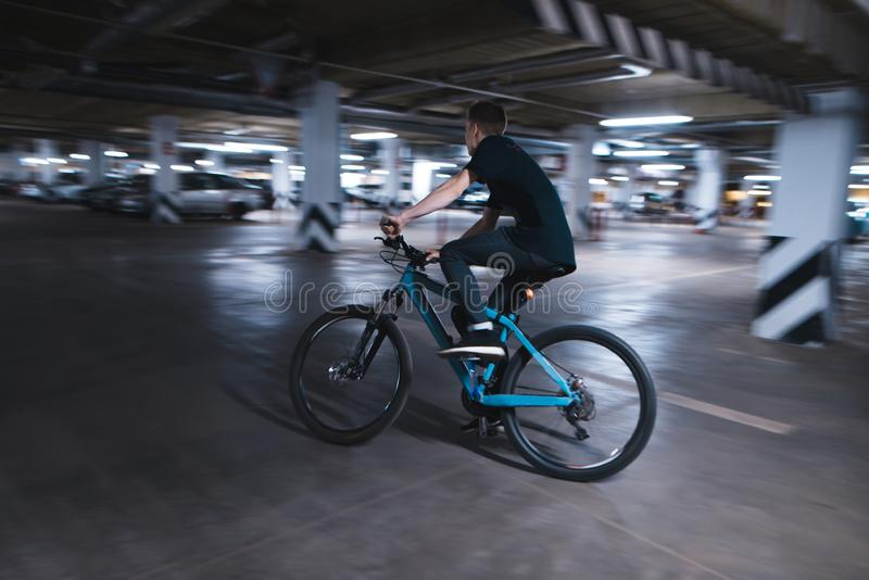 Young man on a blue bike rides through an underground parking lot. Cyclist can ride in an underground parking lot royalty free stock images