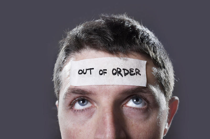 Young man with blue eyes and tape text out of order on forehead in dry empty mind. Young man with blue eyes and tape text out of order on forehead in empty mind royalty free stock image